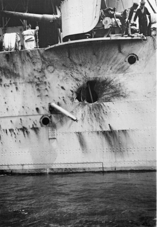 Sailors point to a shell-hole in the side of HMS CHESTER after the Battle of Jutland, 31 May 1916 © IMW/Surgeon Parkes Collection