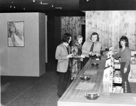 Barmaid Sally Sweeney with customer leaning on bar Jack Lowther - The Barbarella Club, 1972.