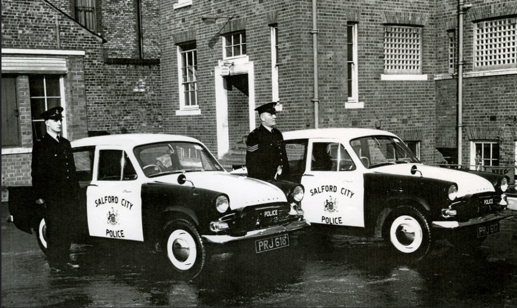 Salford City Police officers display their Hillman Minx patrol cars in the rear yard of their headquarters - © Greater Manchester Police Museum
